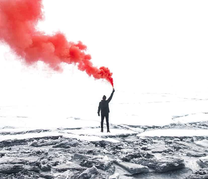 Mann mit Fackel macht roten Rauch
