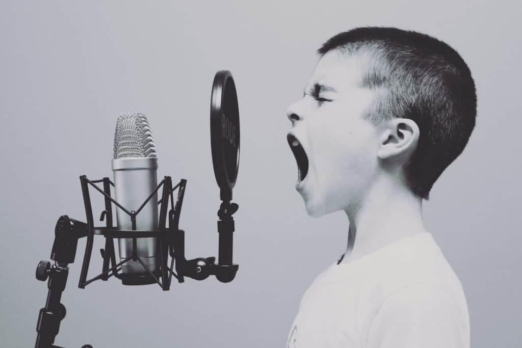 Kind steht mit offenem Mund vor einem Mikrofon